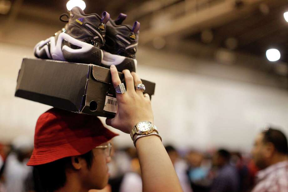 Bryan Shem holds up shoes for sale during the 2013 H-Town Sneaker Summit at Reliant Center in Houston, Texas. Photo: © TODD SPOTH PHOTOGRAPHY, LLC / © TODD SPOTH PHOTOGRAPHY, LLC