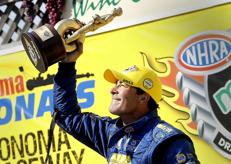 Ron Capps waves his trophy at the crowd after his Funny Car win in Sonoma. Photo: Brant Ward, The Chronicle