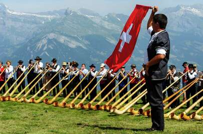 NENDAZ, SWITZERLAND - JULY 28:  A man throws a Swiss flag as alphorn players perform on July 28, 2013 in Nendaz, Switzerland. About 150 alphorn blowers performed together on the last day of the international Alphorn Festival of Nendaz. The Swiss folkloric wooden wind instrument was used in most mountainous regions of Europe by mountain dwellers as signal instruments.