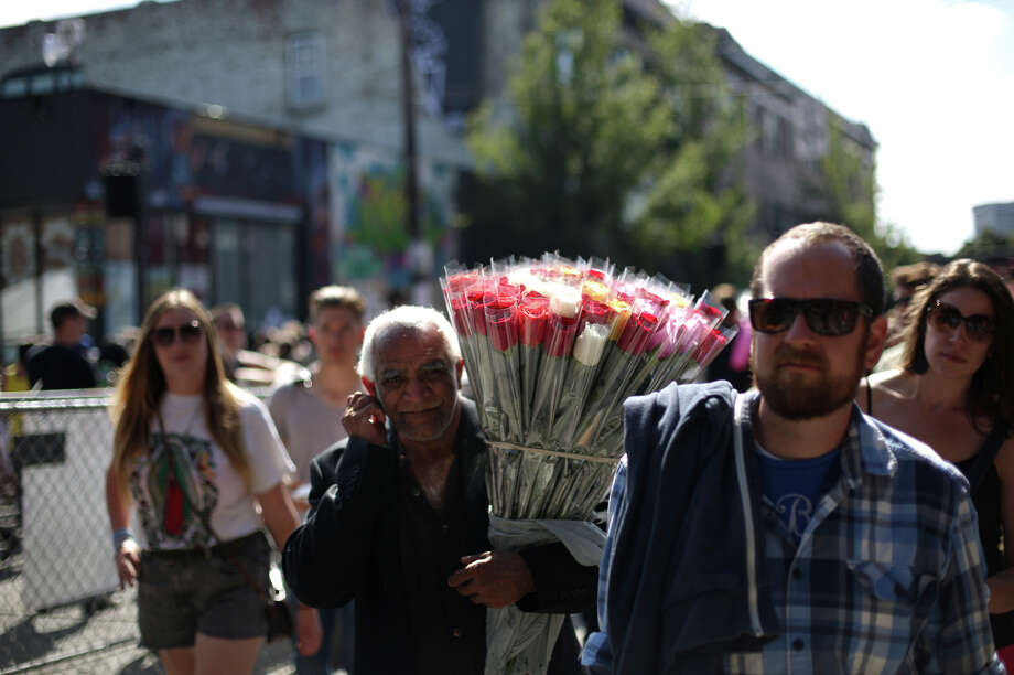 A rose vendor carries flowers for sale during the annual Capitol Hill Block Party on Sunday, July 28, 2013 in Seattle. The three day music festival wrapped up on Sunday. Photo: JOSHUA TRUJILLO, SEATTLEPI.COM / SEATTLEPI.COM