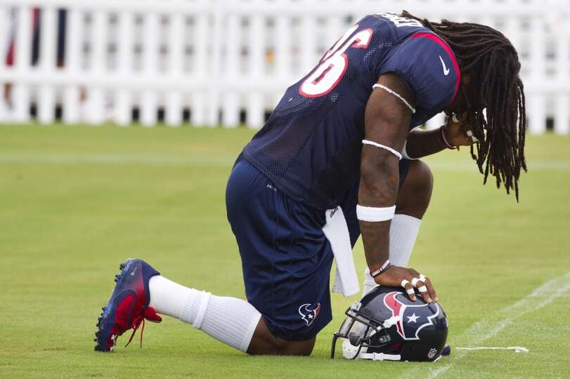 Texans safety D.J. Swearinger kneels down to pray before the start of the third day of training camp