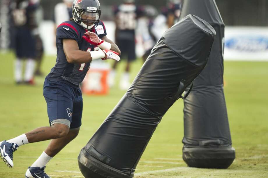 Texans linebacker Justin Tuggle fights through blocking dummies at training camp. Photo: Brett Coomer, Houston Chronicle