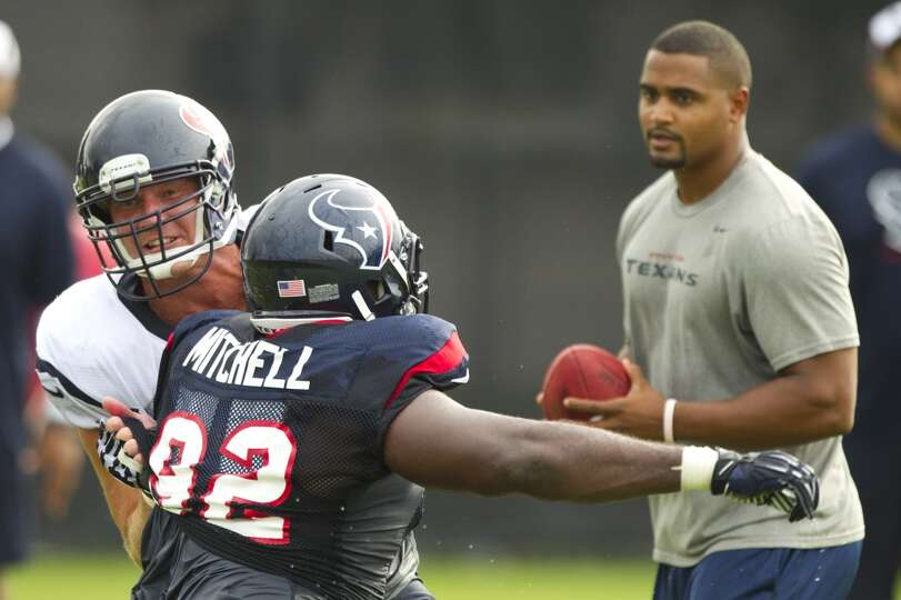 Texans defensive lineman Earl Mitchell participates in a drill with offensive lineman Chris Myers.