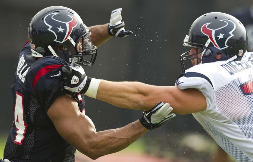 Texans linebacker Trevardo Williams and offensive lineman David Quessenberry participate in a drill