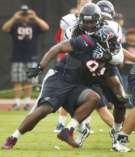 Texans defensive end Antonio Smith participates in a drill with offensive lineman Derek Newton at tr