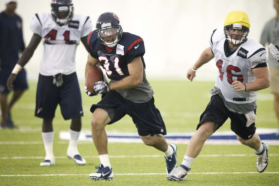 Texans defensive back Shiloh Keo runs past running back Cierre Wood and long snapper Jon Weeks during a special teams drill at training camp. Photo: Brett Coomer, Houston Chronicle