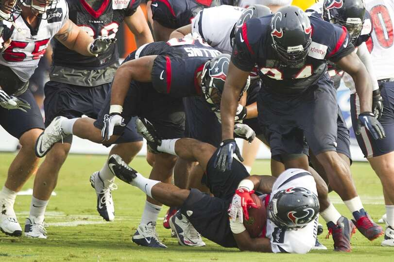 Texans running back Dennis Johnson is tackled by linebacker Cameron Collins.