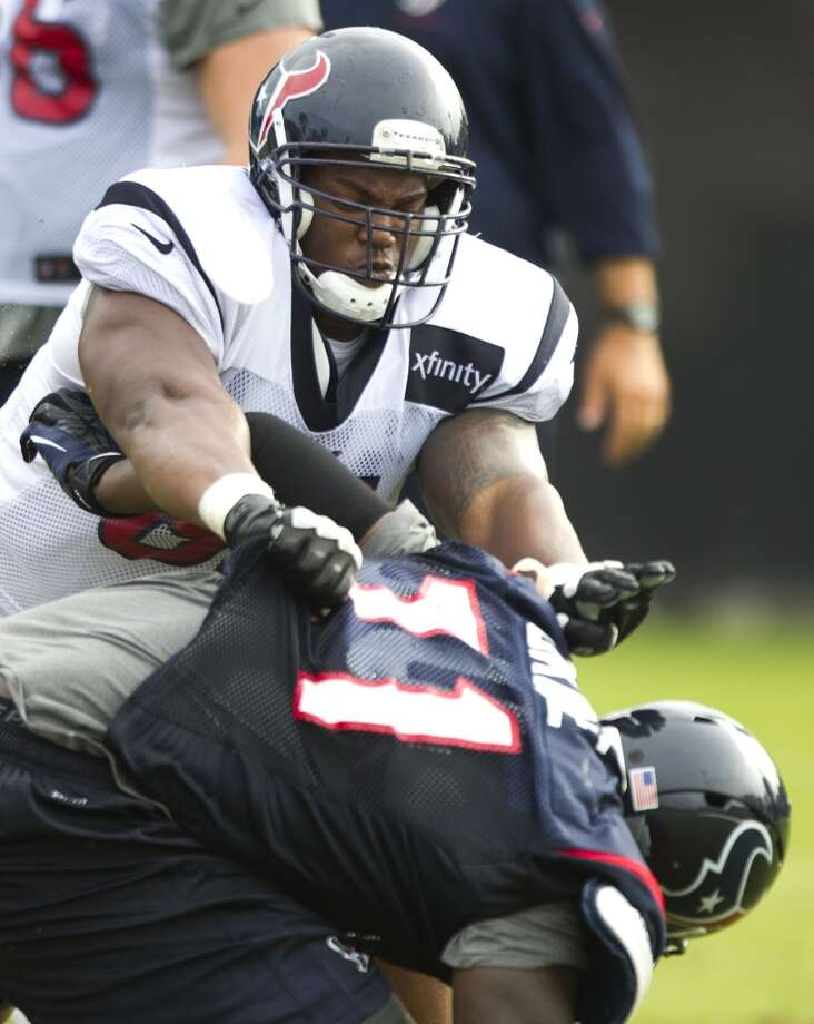 Texans guard Bryan Collins (61) pushes defensive end Earl Okine (71) to the ground. Photo: Brett Coomer, Houston Chronicle