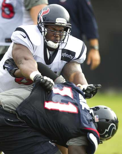 Texans guard Bryan Collins (61) pushes defensive end Earl Okine (71) to the ground.