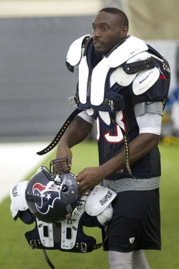 Texans rookie linebacker Willie Jefferson is loaded up with veterans' shoulder pads as he carries th