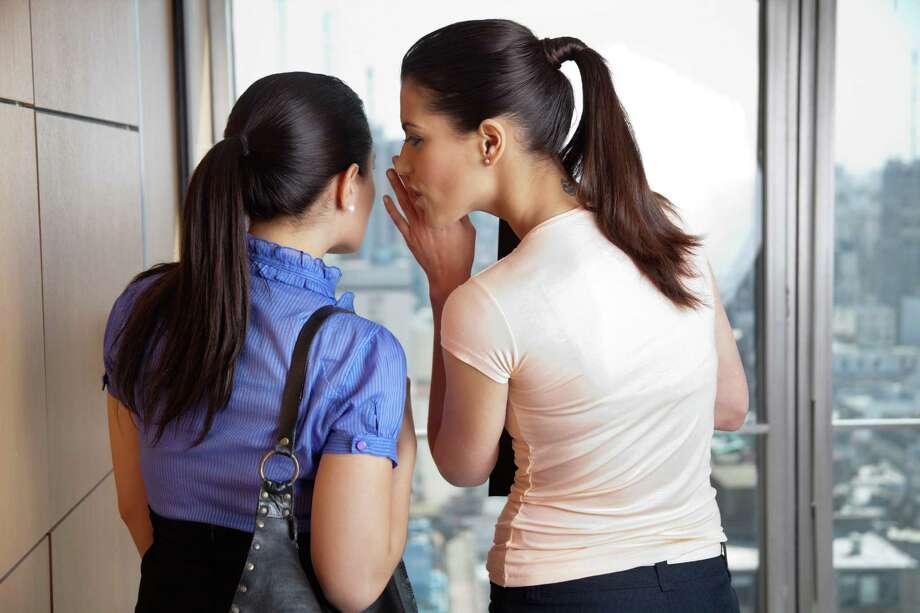Two female co-workers whispering in office Photo: Tyler Olson - SimpleFoto / Tyler Olson - Fotolia