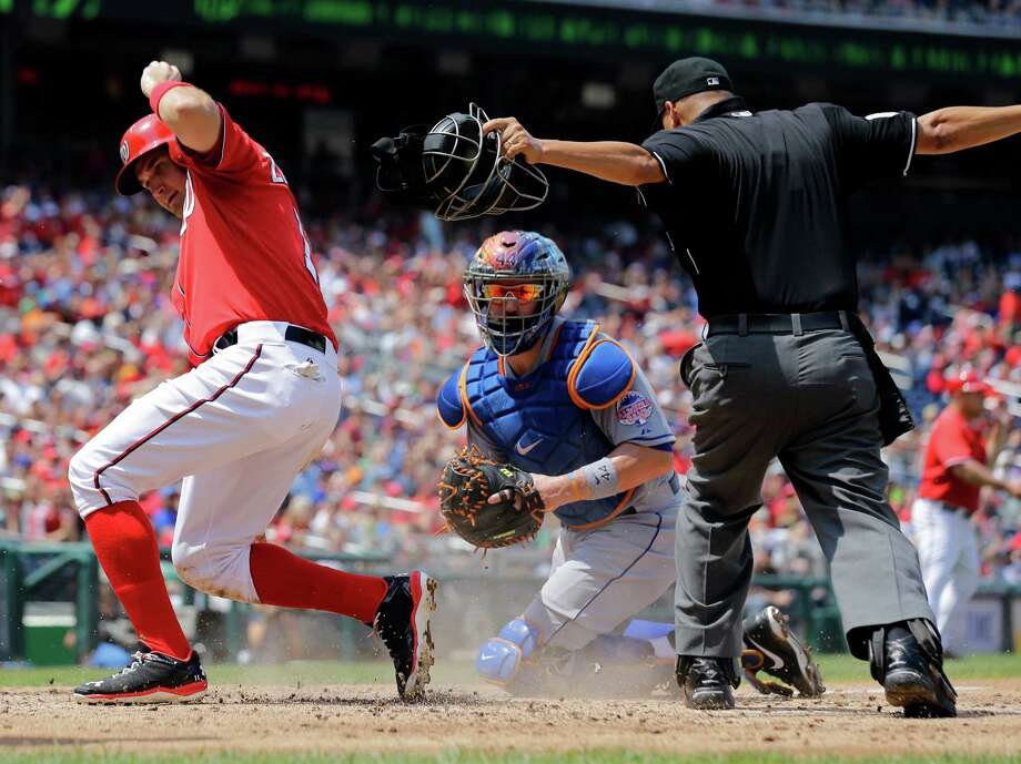 Washington Nationals' Ryan Zimmerman, left, is signaled safe by home plate umpire Vic Carapazza, right, as New York Mets catcher John Buck, center, holds the ball during the third inning of a baseball game at Nationals Park, Sunday, July 28, 2013, in Washington. (AP Photo/Alex Brandon) ORG XMIT: NAT109 Photo: Alex Brandon / AP