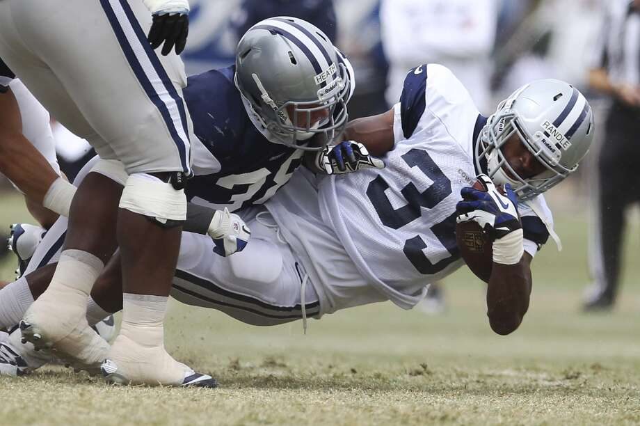 Running back Joseph Randle (35) gets tackled by safety Jeff Heath (38) during practice and the Blue-White scrimmage at the 2013 Dallas Cowboys training camp on Sunday, July 28, 2013 in Oxnard, Calif. (Kin Man Hui / San Antonio Express-News) Photo: Kin Man Hui, San Antonio Express-News