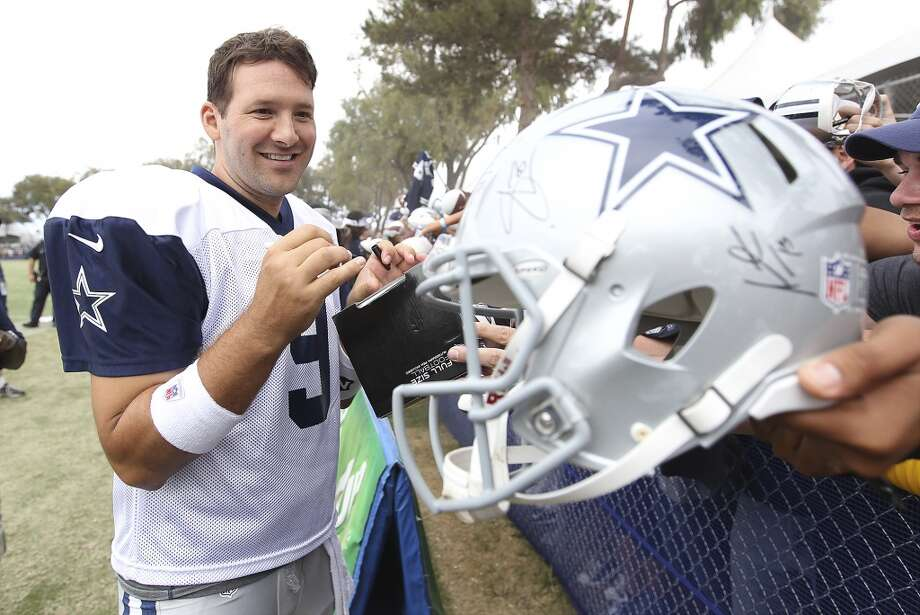 Tony Romo signs autographs after practice and the Blue-White scrimmage at the 2013 Dallas Cowboys training camp on Sunday, July 28, 2013 in Oxnard, Calif. (Kin Man Hui / San Antonio Express-News) Photo: Kin Man Hui, San Antonio Express-News