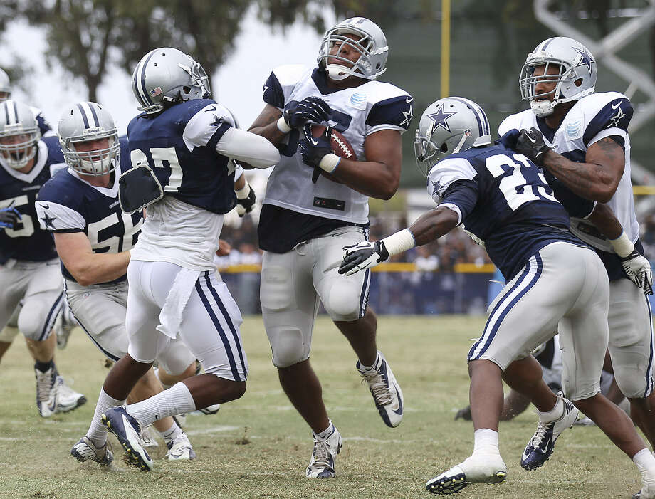Cowboys tight end Andre Smith (with ball) is hit by safety J.J. Wilcox (27) during the Blue-White scrimmage at training camp. Photo: Kin Man Hui / San Antonio Express-News