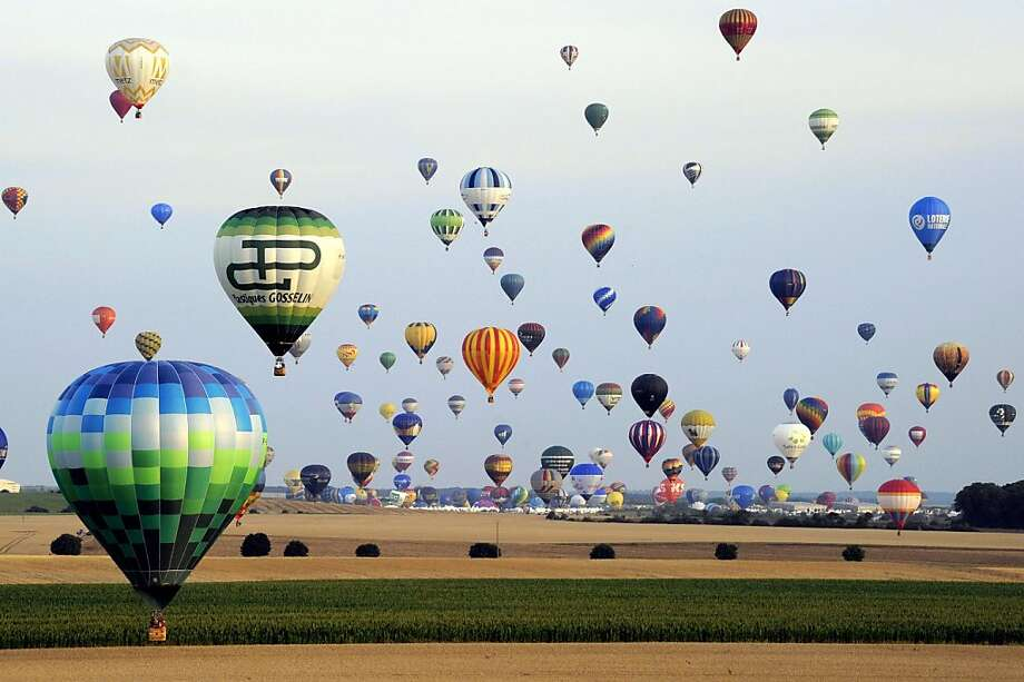"""TOPSHOTS Hot air-balloons fly over a field of sunflowers in Chambley-Bussieres, eastern France on July 27, 2013 as part of the yearly event """"Lorraine Mondial Air  Ballons"""", an international air-balloon meeting. Around 363 to 373 air-balloons took part to the take-off in a try to set a worl record. AFP PHOTO /POOL ALEXANDRE MARCHIALEXANDRE MARCHI/AFP/Getty Images Photo: Alexandre Marchi, AFP/Getty Images"""