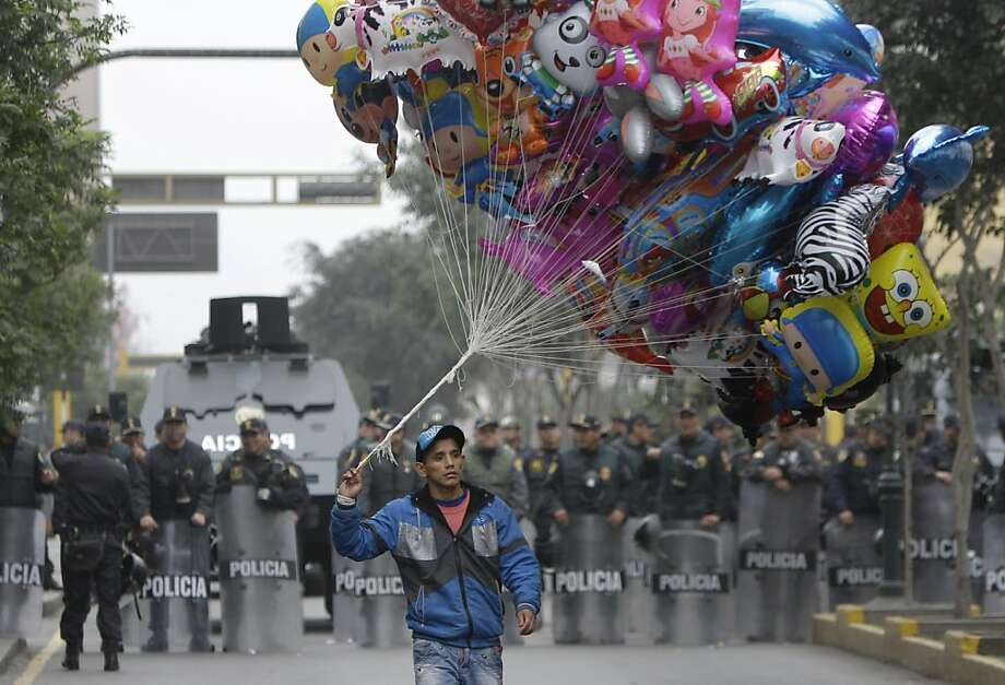 A balloon vendor walks in front of a group of riot police standing guard during an anti-government demonstration that was taking place as Peru's President Ollanta Humala delivered his State of the Nation address, in Lima, Peru, Sunday, July 28, 2013. Demonstrators claim Humala has not delivered on his promises to reduce crime and they say the political system does not represent them. (AP Photo/Martin Mejia) Photo: Martin Mejia, Associated Press