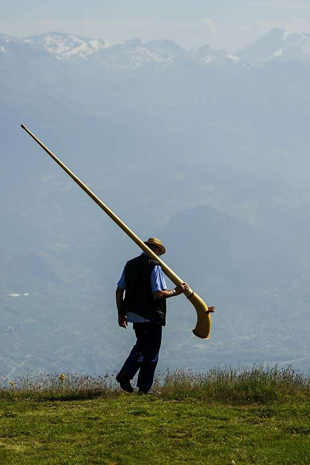 NENDAZ, SWITZERLAND - JULY 28:  An alphorn player walks in a grassland on July 28, 2013 in Nendaz, Switzerland. About 150 alphorn blowers performed together on the last day of the international Alphorn Festival of Nendaz. The Swiss folkloric wooden wind instrument was used in most mountainous regions of Europe by mountain dwellers as signal instruments.  (Photo by Harold Cunningham/Getty Images) *** BESTPIX *** Photo: Harold Cunningham, Getty Images