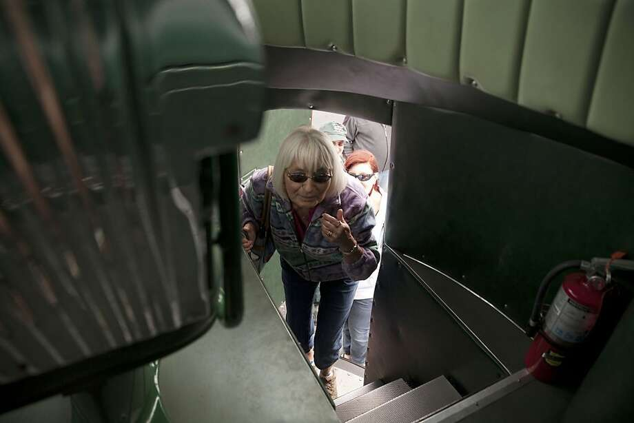 Burton resident Irene Rexford climbs into a 1953 GM Futurliner during a Classic & Antique Semi-Truck Show on Sunday, July 28, 2013 at Baker College's Center for Transportation Technology. The Futurliner was designed to display the modern technologies of its age, such as microwave ovens and jet engines. Of the 12 Futurliners that were built , only nine are known to exist today. The event showcased a unique series of vehicles 25 years or older. (AP Photo/MLive.com, Michelle Tessier) Photo: Michelle Tessier, Associated Press