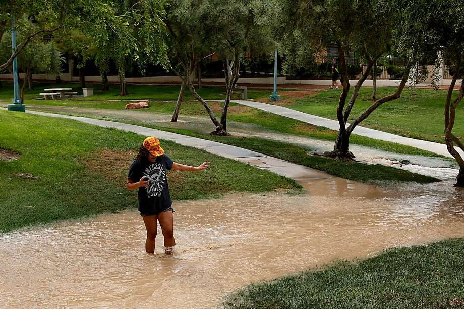 Julie Vickers wades across flood waters on a trail along Apple Dr. in Las Vegas Saturday, July 28, 2013. Heavy rains caused flash flooding in parts of the Las Vegas valley. (AP Photo/Las Vegas Review-Journal, John Locher) Photo: John Locher, Associated Press