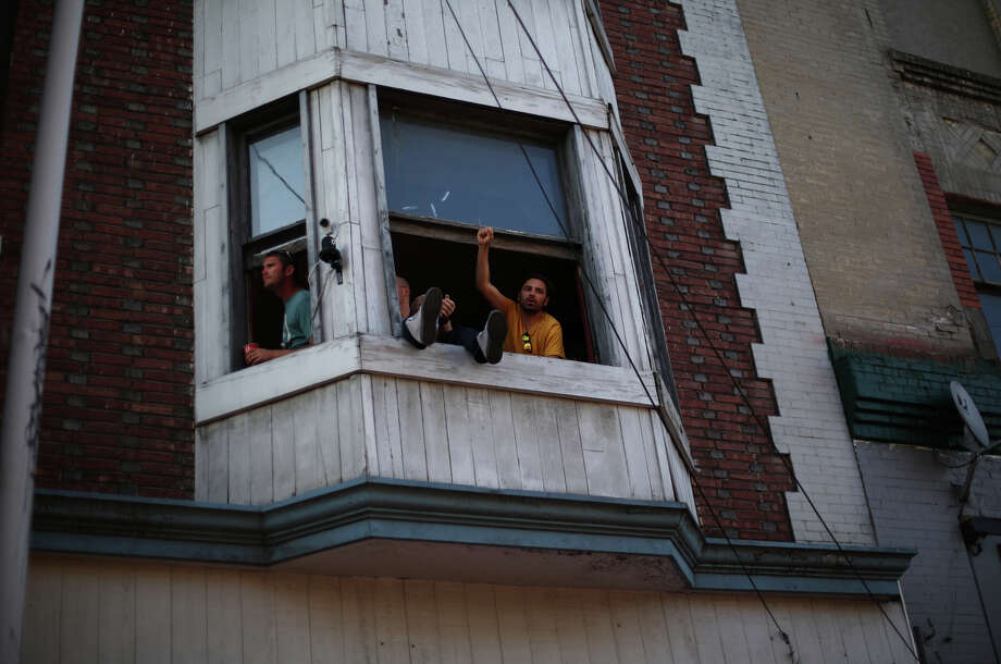 People watch the action from an apartment during the annual Capitol Hill Block Party on Sunday, July 28, 2013 in Seattle. The three day music festival wrapped up on Sunday. Photo: JOSHUA TRUJILLO, SEATTLEPI.COM / SEATTLEPI.COM