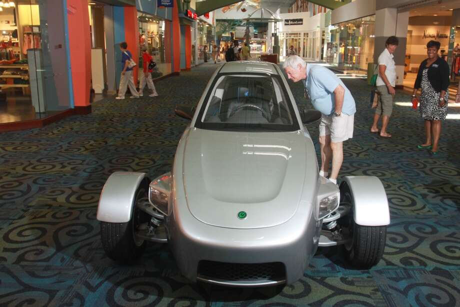 Bruce Parker looks at the Elio, a three-wheeled vehicle on display at Katy Mills shopping center. Photo: Gary Fountain, For The Chronicle