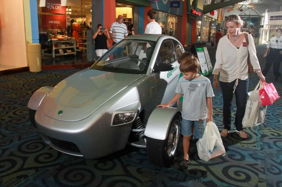 Tina Kristof and her son Alex, 7, looking at an Elio, a three-wheeled vehicle on display at Katy Mills shopping center. Standing behind Alex is another son, Joaquin, 6. Photo: Gary Fountain, For The Chronicle