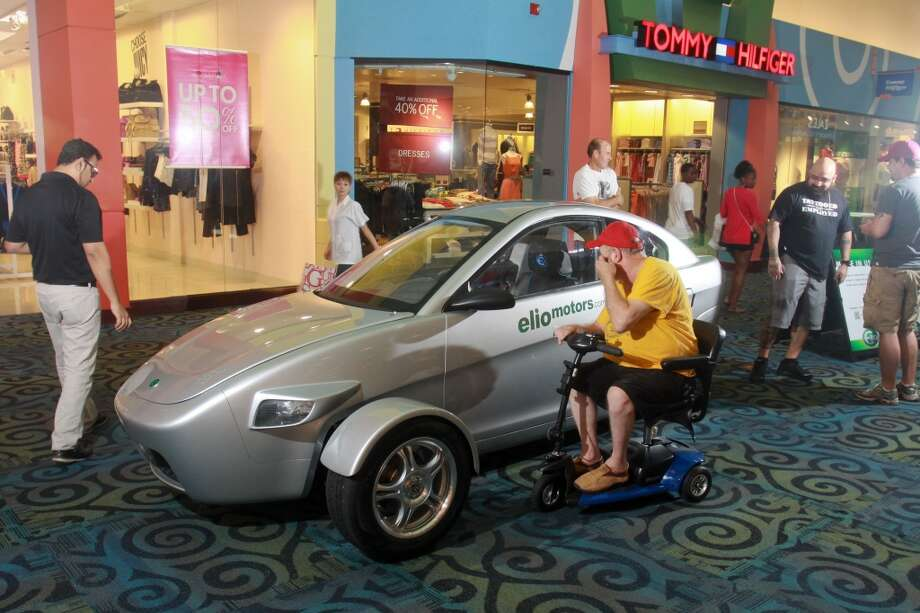 Joe Foty looks at an Elio, a three-wheeled vehicle on display at Katy Mills shopping center. Photo: Gary Fountain, For The Chronicle