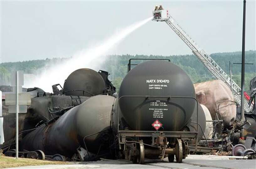 Firefighters water railway cars the day after a train derailed causing explosions of railway cars ca
