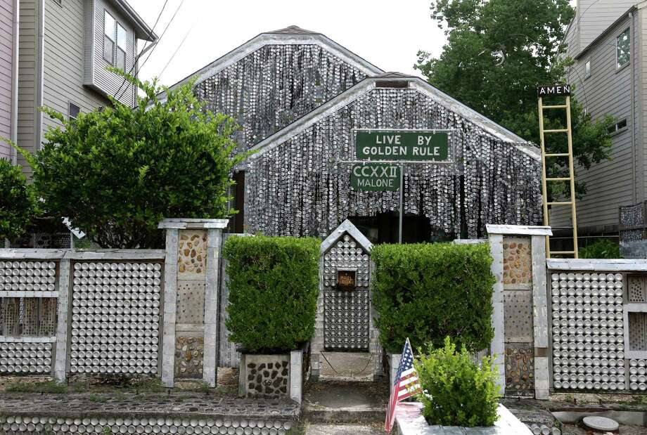 The beer can house, a Houston landmark, sits between newer homes Wednesday, July 10, 2013, in Houston. Former owner John Milkovisch covered the outside on the house with siding made of cut and flatten beer cans and garlands made from the lids. The Orange Show Center for Visionary Art, a local nonprofit that preserves art installations in the city, bought the property about 10 years ago, restored the house and it opened it to the public. (AP Photo/Pat Sullivan) Photo: Pat Sullivan, STF / AP