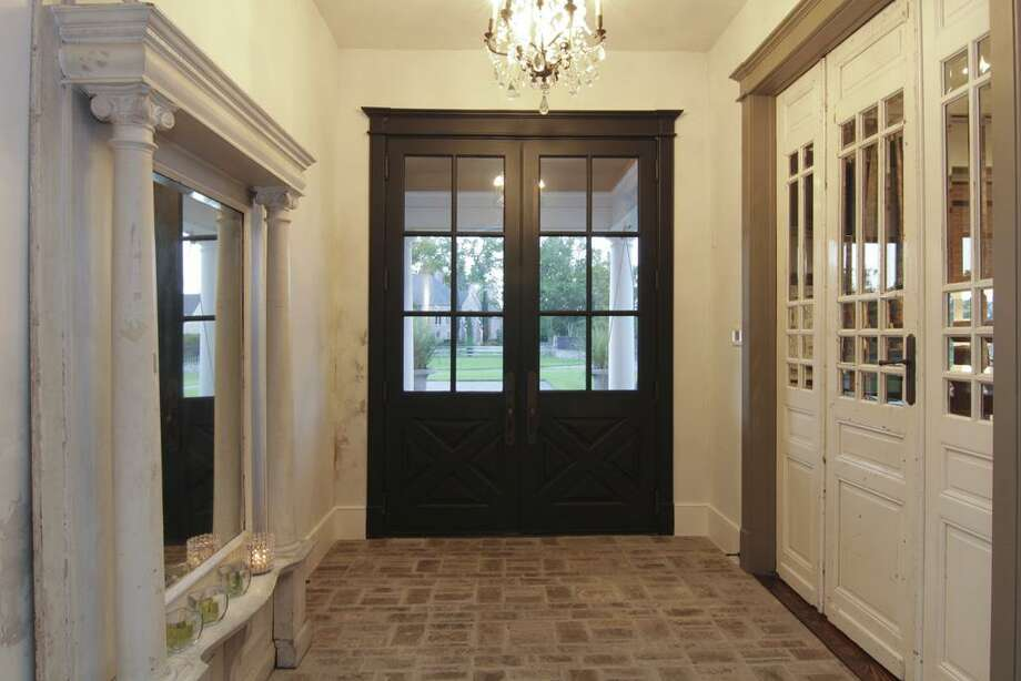 The entry features antique doors and light fixture.