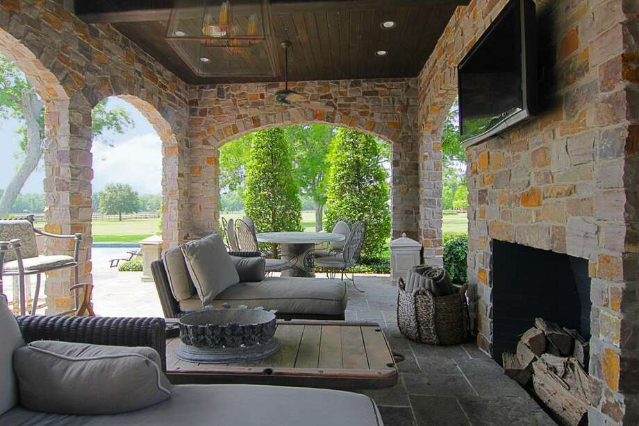 Outdoor seating area with fireplace and flatscreen TV.
