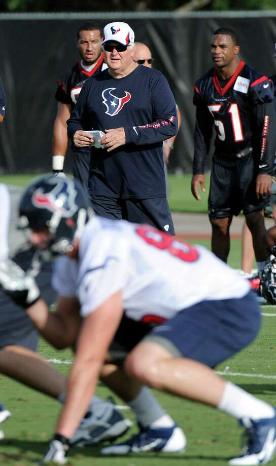 Houston Texans defensive coordinator Wade Phillips, top center, and Darryl Sharpton (51) watch workouts during NFL football training camp Friday, July 26, 2013, in Houston. (AP Photo/Pat Sullivan) Photo: Pat Sullivan, STF