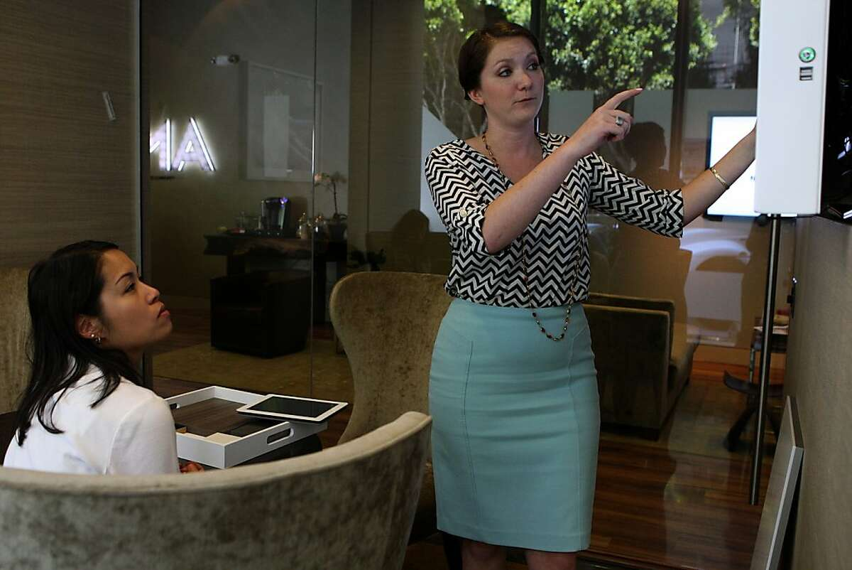 Leasing agent Kelly Lombardi (right) shows client Bonnie Dong (left) floor plans for one bedroom apartments at NeMa in San Francisco, Calif., on Wednesday, July 24, 2013. NeMa is a new residential building opening in October designed by Glenn Rescalvo with four linked towers ranging from 10 to 37 stories