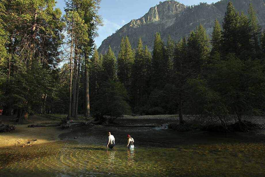 Visitors wade into the Merced River at Yosemite National Park, the second-best national park in the United States to Yellowstone. We say that's a fair assessment. Photo: Jim Wilson, New York Times