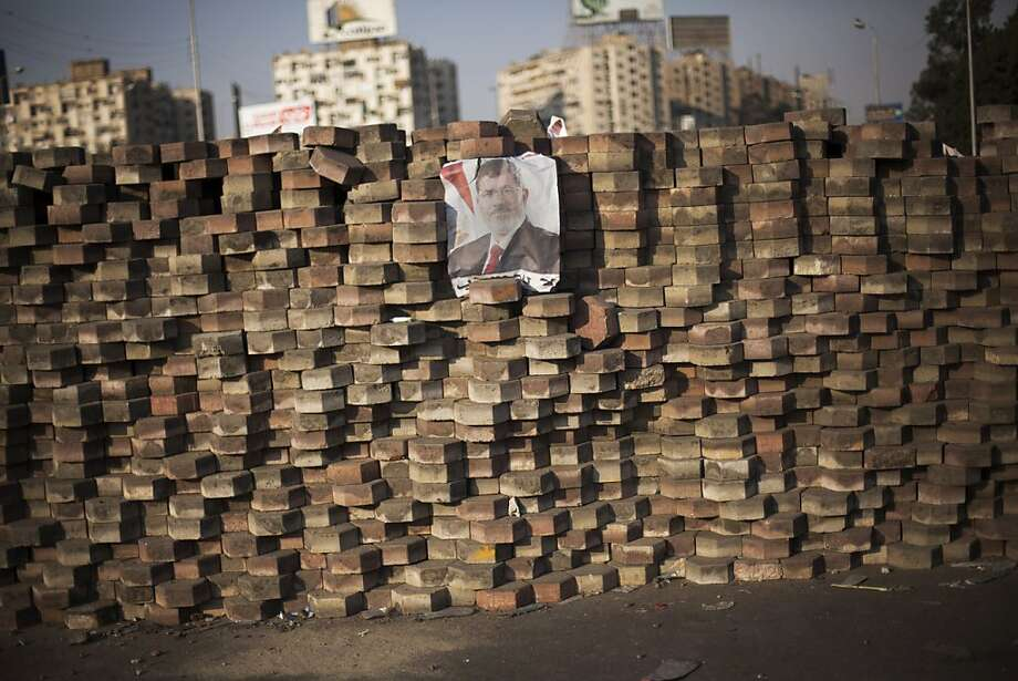 A picture of ousted President Mohammed Morsi decorates a barricade in Nasr City, a district of Cairo, where rallies in support of Morsi have turned bloody. Photo: Manu Brabo, Associated Press