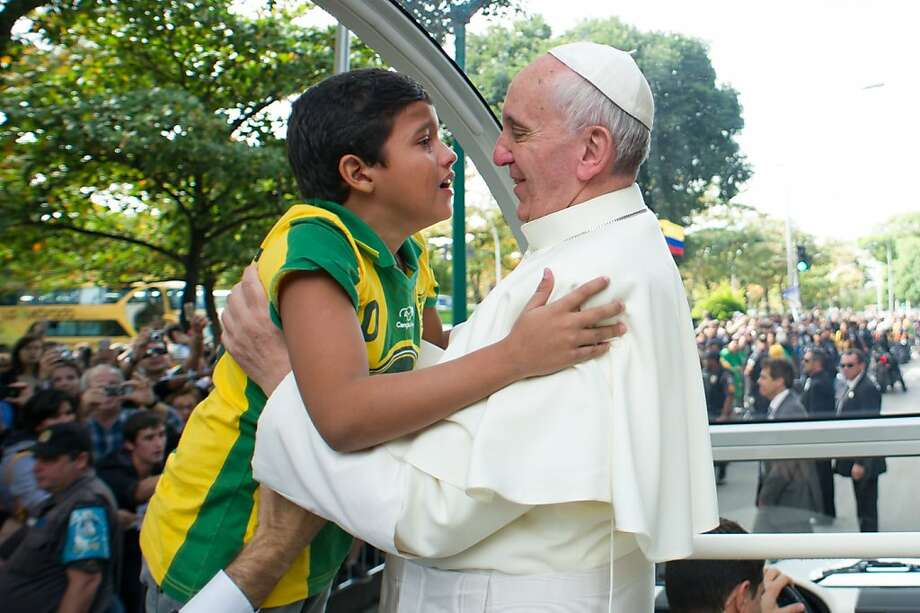 Pope Francis hugs a boy in Rio de Janeiro before returning to Rome on Sunday. Photo: Luca Zennaro, AFP/Getty Images