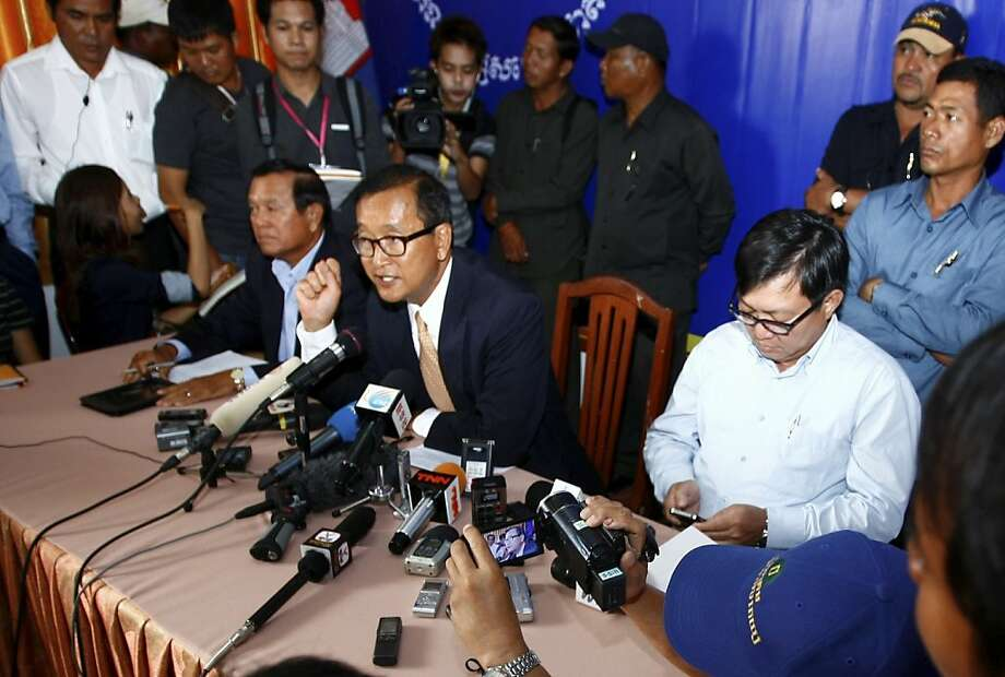 Cambodia National Rescue Party (CNRP) President Sam Rainsy, center, speaks during a press conference in his main party headquarters in Chak Angre Leu in Phnom Penh, Cambodia, Monday, July 29, 2013. Cambodia's opposition party CNRP said Monday it would challenge the results of a general election in which it made impressive gains even though the ruling party of Prime Minister Hun Sen retained power. (AP Photo/Heng Sinith) Photo: Heng Sinith, Associated Press