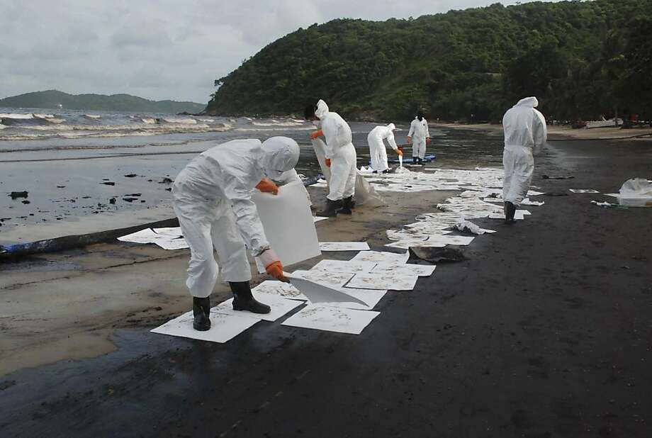 Workers remove crude oil on the beach of Prao Bay on Samet Island in Rayong province eastern Thailand Monday, July 29, 2013. The oil spill that leaked from a pipeline has reached the popular tourist island in Thailand's eastern sea despite continuous attempts to clean it up over the weekend, officials said Monday. (AP Photo/Daily News) **Thailand Out** Photo: Associated Press