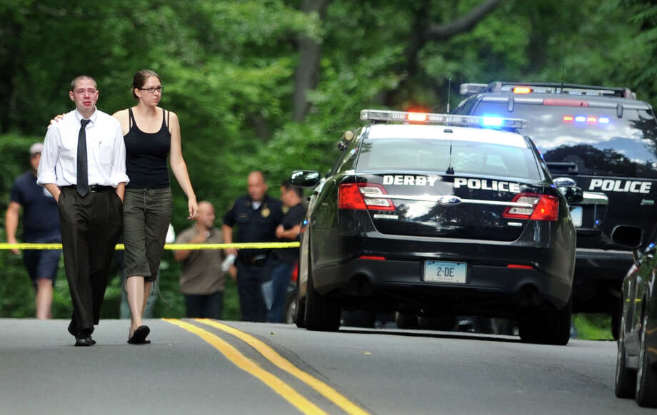 A man and a woman walk down Roosevelt Drive after visiting the scene of a fatal accident in Derby, Conn., July 29, 2013. One woman was killed when her SUV collided with a tractor-trailer. Photo: Ned Gerard / Connecticut Post