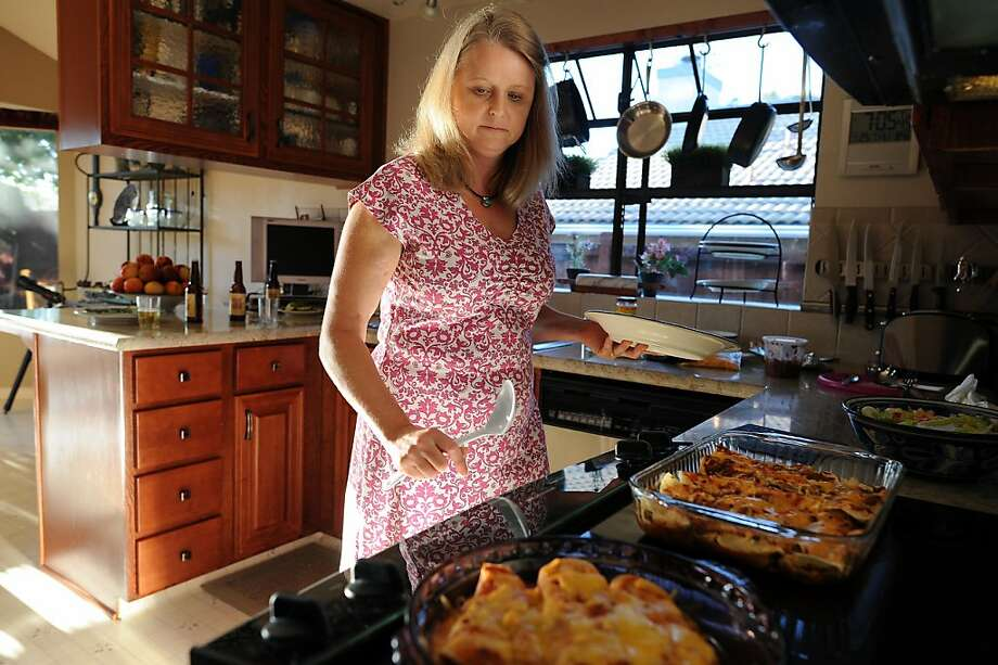 Lynn Opp, who has celiac disease, fixes a gluten-free meal with special chicken enchiladas at her home. Photo: Michael Short 2013, Special To The Chronicle