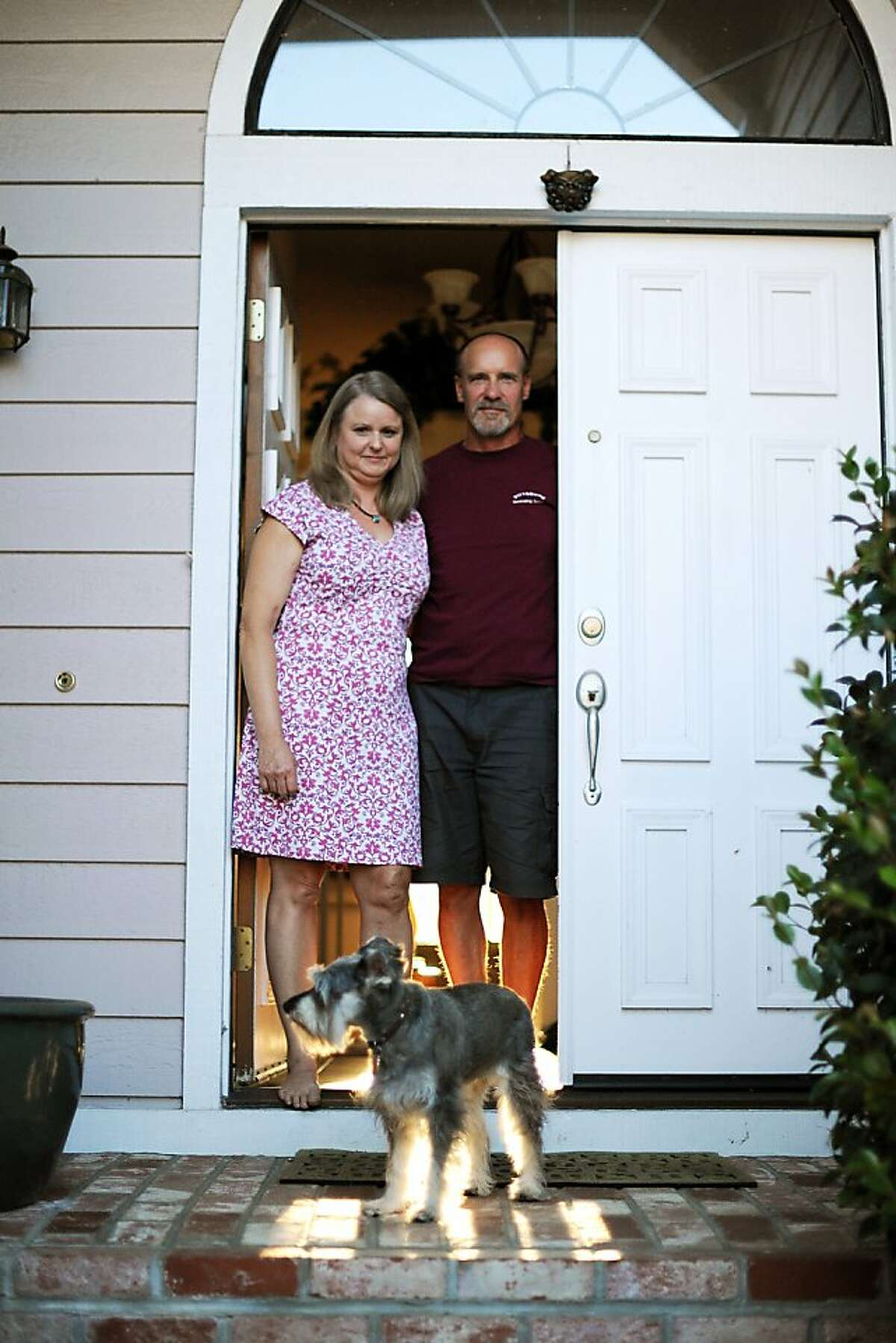 Lynn Opp, diagnosed with the auto-immune disorder Celiac disease, and her husband Alan Opp stand at their front door with their dog Katie at their home in Concord, California, Thursday, July 25, 2013.