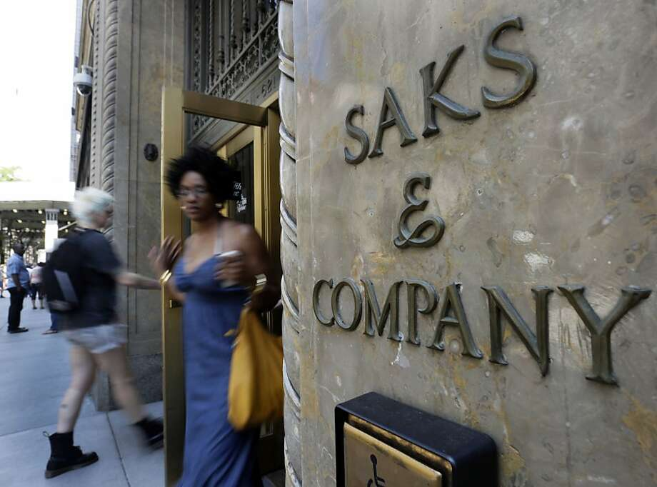 Shoppers use a Fifth Avenue entrance to Saks, in New York,  Monday, July 29, 2013. Saks Inc. agreed to sell itself to Hudson's Bay Co., the Canadian parent of upscale retailer Lord & Taylor, for about $2.4 billion in a deal that will bring luxury to more North American locales. (AP Photo/Richard Drew) Photo: Richard Drew, Associated Press