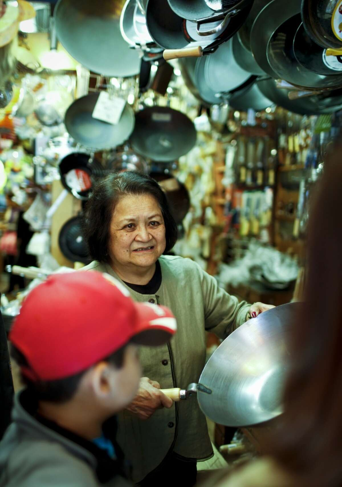 Tane Chan, the owner of Chinatown's Wok Shop since 1972 assists customers. She is the subject of a profile in the Chronicle's Food & Wine section.