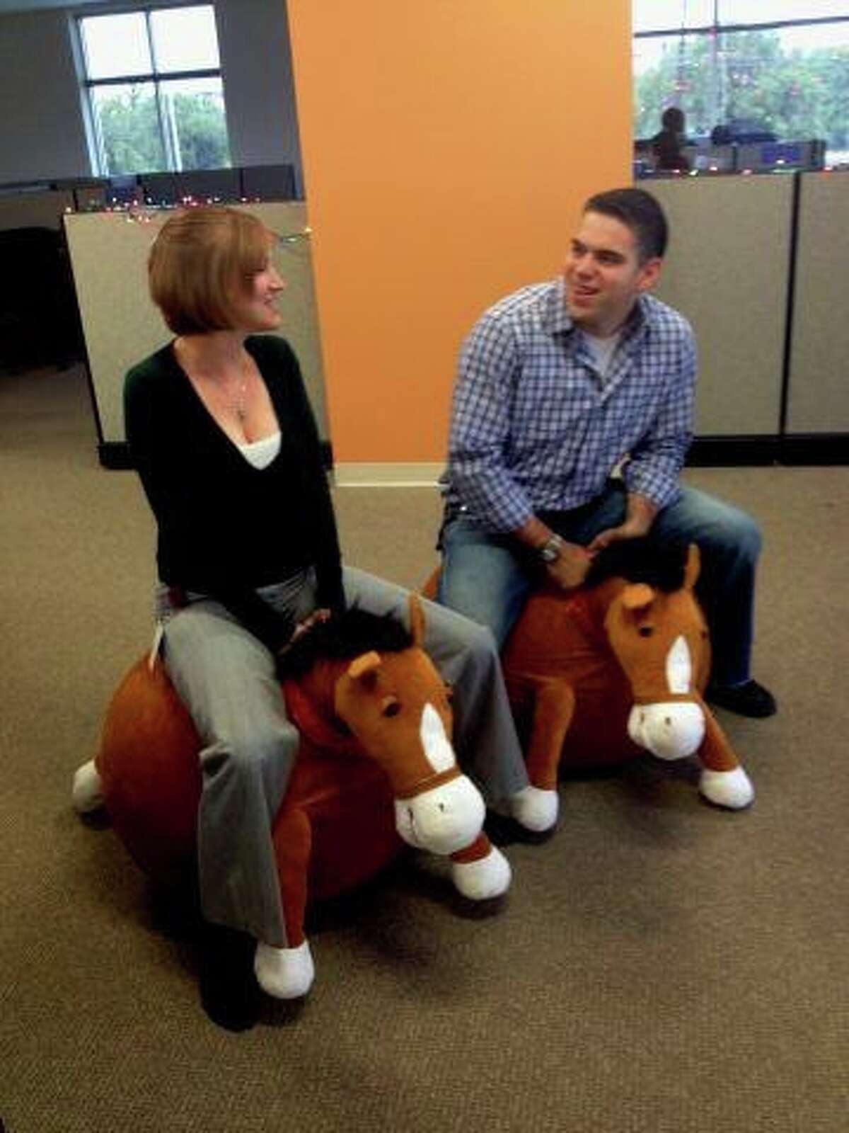 Amanda Bayane, left, and Javier Cano use the bouncing horses to get around the halls at Hostway.