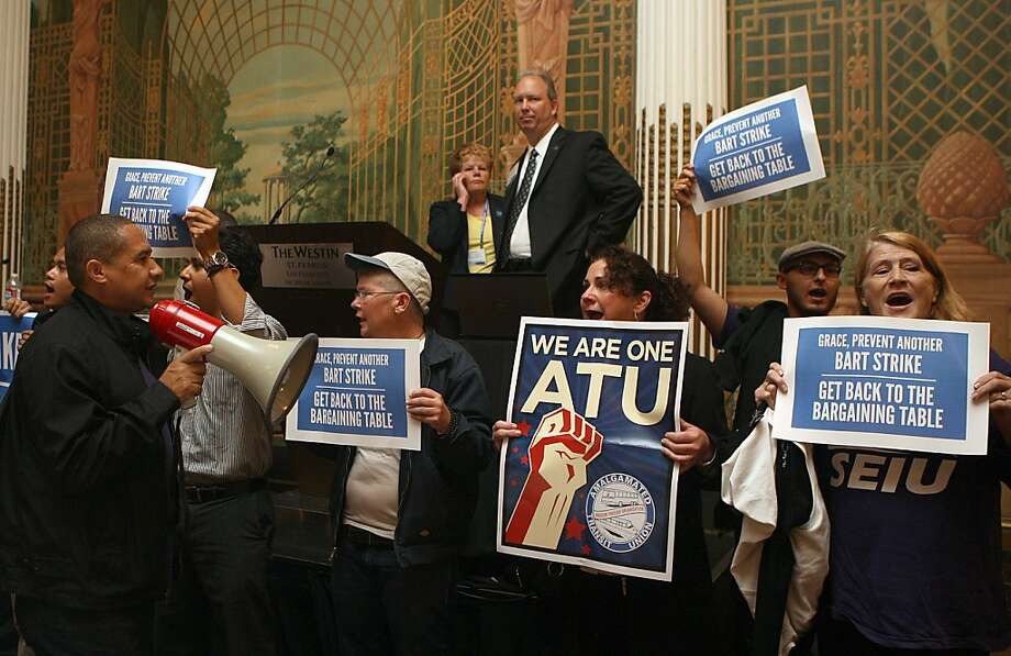 BART chief Grace Crunican (rear, left) watches as union workers protest at a transit industry convention in S.F. Photo: Liz Hafalia, The Chronicle