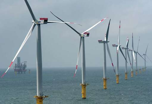"""BORKUM, GERMANY - JUNE 23:  Wind turbines stand at the nearly completed Riffgat offshore wind farm in the North Sea on June 23, 2013 near Borkum, Germany in front of the jack-up installation vessel """"Bold Tern"""". The Riffgat facility includes 30 turbines with a capacity of 3.6 megawatts each for a total output of 108 megawatts, enough to provide power to 120,000 households. Germany is pursuing the construction of offshore wind farms in the North Sea as well as the Baltic Sea, though some projects have been hampered by a lack of adequate undersea cables to bring the power on shore. Photo: David Hecker, Getty Images / 2013 Getty Images"""