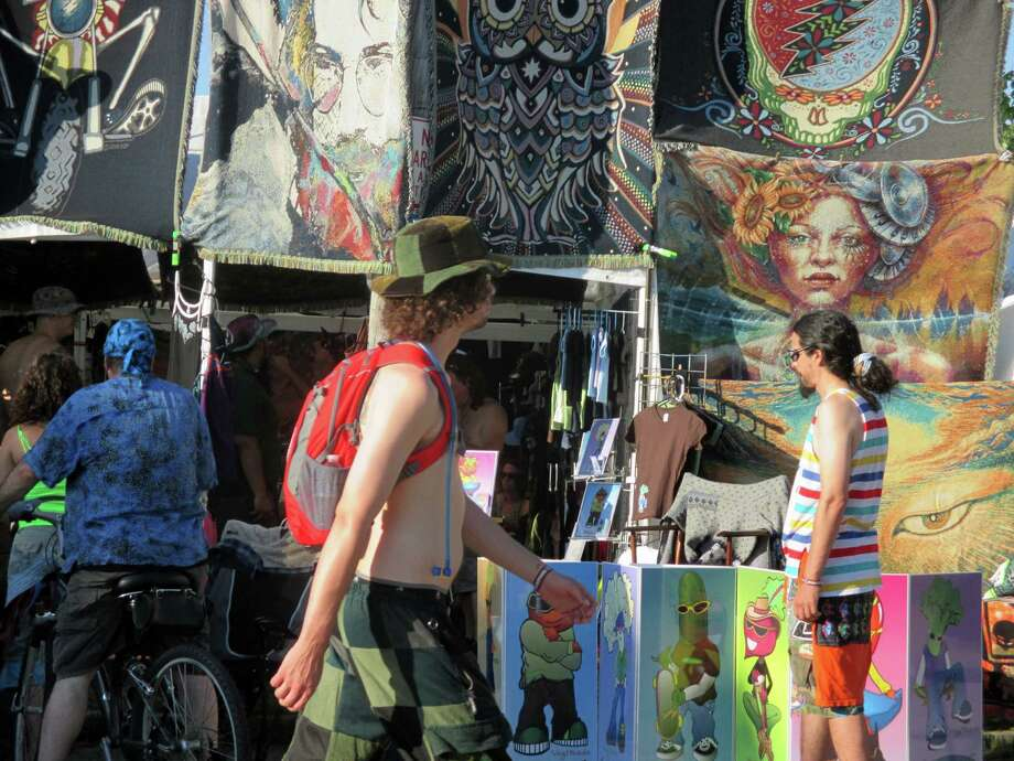 In this Friday, July 26 photo released by Paul Duning, a music fan at the Gathering of the Vibes festival walks by a vendor selling souvenirs including one with the image of the late Jerry Garcia, the Grateful Dead guitarist who died in 1995. The festival draws about 20,000 fans to this small city on the Connecticut coast and features a wide variety of bands including offshoots of the Grateful Dead. (AP Photo/Paul Duning) ORG XMIT: NYET703 Photo: Paul Duning / Paul Duning