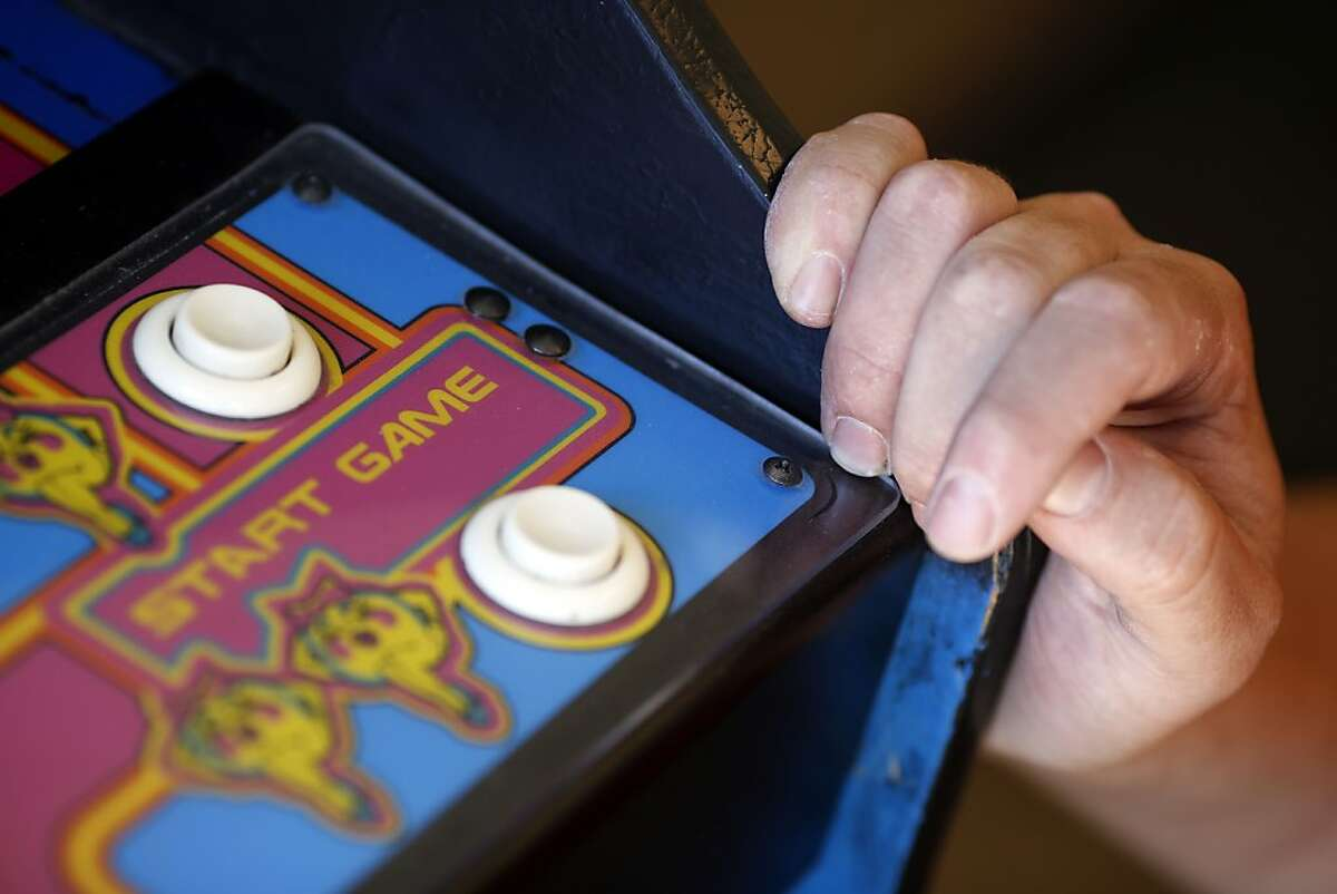 Tim Peterson holds on to Ms. Pac-Man while turning it on in a home he delivered it to in El Granada, Calif. on July 24, 2013.