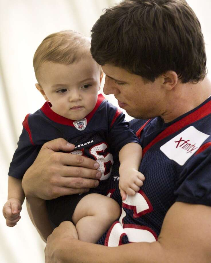Inside linebacker Brian Cushing holds his son Cayden at the end of practice. Photo: Brett Coomer, Chronicle
